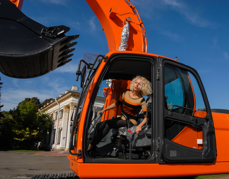 A young blond hair woman sits in a cabin of a new orange crawler excavator with a big bucket and looks forward. The photo was shot in the park, Kiev, Ukraine.
