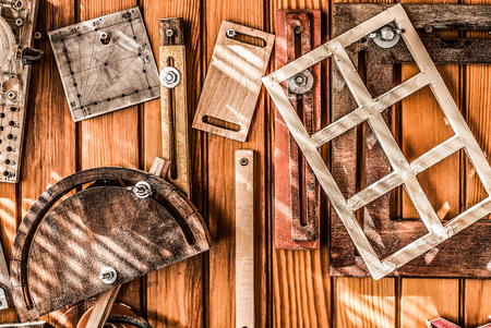 An amber background with wooden and metal tools hanging on the wooden wall. It's all about hobby of a carpenter.