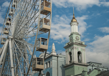 A view of a ferris wheel and the Bell Tower of the orthodox Church of St. Catherine the Great Martyr, located at the Contract Square, Kiev, Ukraine. Concept - modern is close to old.  Stock Photo