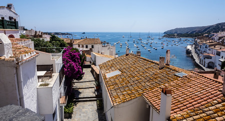 A beautiful view of the Mediterranean sea from the red tiled rooftops of white houses on the seashore, Cadaques, Spain.