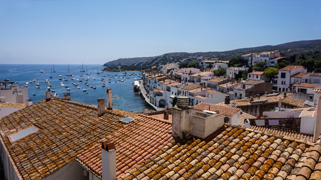 A beautiful seascape of the Mediterranean sea from the red tiled rooftops of white houses, standing on the seashore of  the resort town, Cadaques, Spain. Concept - paradise place for beloved and artists.