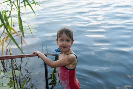 A nice four-year old girl stands smiling in the river. Child in a red swimsuit has a beautiful eyes, as blue as a water. Concept - nature and happy childhood.