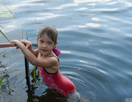 A nice four-year old girl stands holding a handrail in the open water. Child in a red swimsuit has a beautiful eyes, as blue as a water. Concept - vacation and happy childhood.