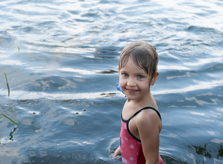 A nice four-year old girl stands smiling and laughing in the open water. Child in a red swimsuit has a beautiful eyes, as blue as a water. Concept - nature and happy childhood.