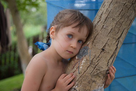 Portrait of a little four-years old girl, bending over a tree trunk. The child looks closely with her beautiful big blue eyes.