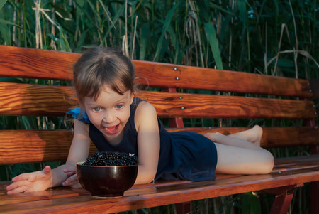 A four-years-old little girl lying on the bench among the high green grasses. The child loooks at a bowl full of fresh ripe blackberries with open mouth. Concept - expression of joy, happiness and surprise.