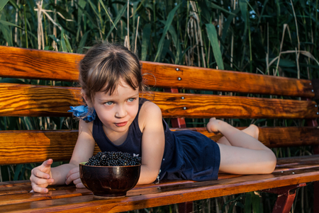 A little girl with beautiful big blue eyes lies on the bench among the high grasses. A bowl full of fresh blackberries stands in front of the child. Concept - healthy food.