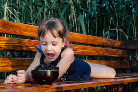 Closeup of a four-years-old girl, lying on the wooden bench. The child looks at a bowl full of blackberries. Her mouth is wide open as she wants very much to eat berries. Concept - healthy food.