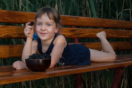 Smiling ittle girl lies on a wooden bench with a berry in her hand. A bowl full of fresh blackberries stands in front of the child.  Concept - happy childhood.