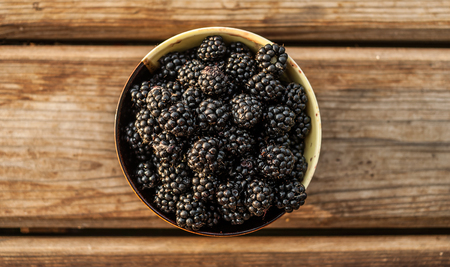 Closeup of a bowl full of fresh ripe blackberries on wooden background. Concept - healthy food. Standard-Bild