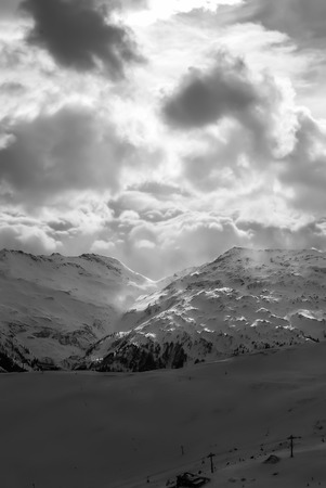Sunlight comes through clouds on the empty snow Alps, Bad Hofgastein, Austria. Top view landscape of lonely ski trails in black and white colors. Standard-Bild
