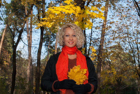 Beautiful blond woman standing under maple tree in autumn park. Smiling pretty woman in orange scarf with yellow maple leaves in her hands. Concept - healthy and natural beauty.