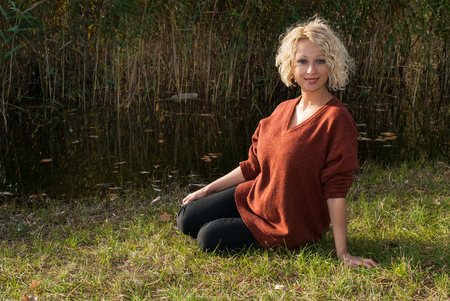 Beautiful blond woman sitting on the grass near lake in autumn park. Smiling curly hair woman in terracotta jumper. Concept - healthy and natural beauty.