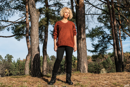 Pretty blond woman standing near pines in autumn park. Curly hair woman in terracotta jumper and black jeans in forest for hiking activity. Concept - sport activity outdoors. Standard-Bild