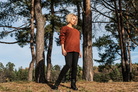 Pretty blond woman standing near pines in autumn park. Curly hair woman in terracotta jumper and black jeans in forest for outdoors activity. Concept - sport activity outdoors.