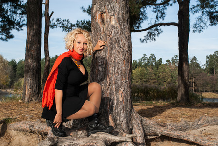Pretty blond hair woman sitting on the big roots of pine tree in coniferous autumn park. Young smiling woman in orange scarf, black dress and heavy boots. Concept -  outdoor activity.