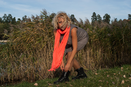 Blond curly hair woman bending over to tie shoelace. Young woman in gray dotted dress, orange scarf and heavy black boots is in autumn park for sport activity. Concept - healthy lifestyle.