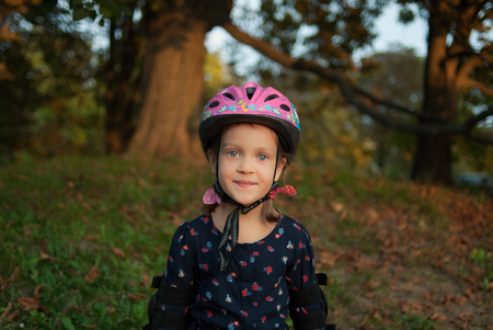 Portrait of a smiling little girl in a helmet and elbow pads. Little roller skater is in outdoor activity in autumn park. Concept - healthy lifestyle.