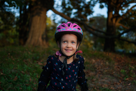 Portrait of a laughing little girl in a helmet and elbow pads. Little roller skater is in outdoor activity in autumn park. Concept - healthy lifestyle.