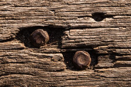Old wooden bench texture, closeup. Aged Solid Wood Slat Rustic Shabby Brown Background With Rusty Nut and Bolt.