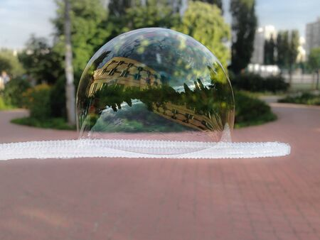 Big soap bubble on a bubble blower. Building and trees reflecting in a huge bubble in a city park.