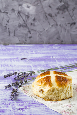 Easter hot cross buns with lavender flowers on napkin and wooden white and violet table. Easter bakery. Stock Photo