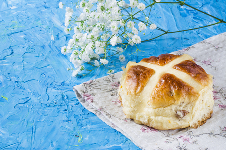 Traditional Easter hot buns on a napkin and sky blue background. Traditional bakery.