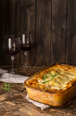 Traditional meat lasagna on wooden background. Red wine in wineglass. Homemade italian lasagna with bolognese and bechamel sause served with arugula. Gray napkin on wooden table. Stock Photo