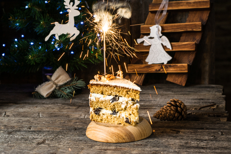 Traditional russian Honey cake. winter composition. christmas photo. New Year decorations. Angel, christmas deer. Xmas decoration. Honeycake with sparklers. garland on christmas tree. Pudding Standard-Bild