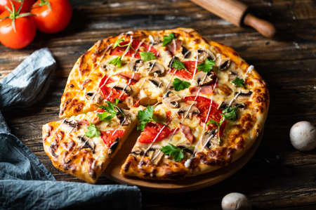 tasty juicy pizza on wooden background. lots of meat and cheese. Mushroom pizza. Pepperoni pizza. Mozzarella and tomato. Italian dish. Italian food