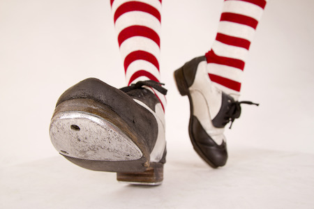 Pair of black and white tap shoes with red and white striped socks Stock Photo
