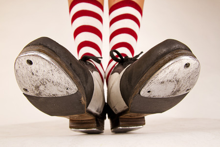 Pair of black and white tap shoes with red and white striped socks Foto de archivo