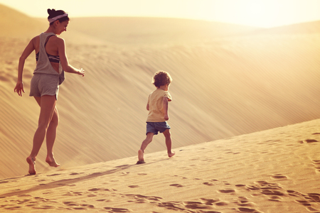 Fit mother with son running at the desert in Gran Canaria, Maspalomas on sunset