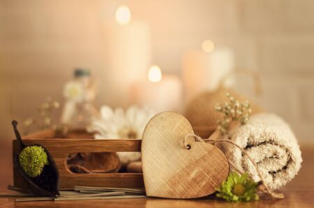 Spa setting with towels, oil, flowers, candles, and wooden heart on white bricks background Stock Photo