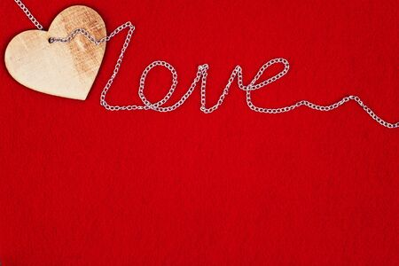 Wooden heart and chain Love on red background for St. Valentines day