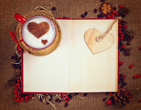 Valentines postcard. Cup of coffee in the red cup with two cinnamon hearts standing on open book with wooden heart and space for your text.