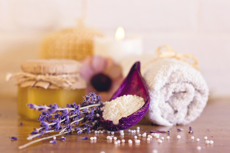 Spa and wellness setting with white towels , sponge, candle, lavender and wooden heart on bricks wall background. Valentines postcard.