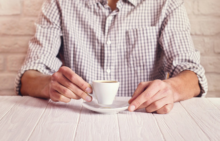 cosy: Coffee break. Man sitting on the white table with cup of espresso in the checked shirt. White bricks wall background. Stock Photo
