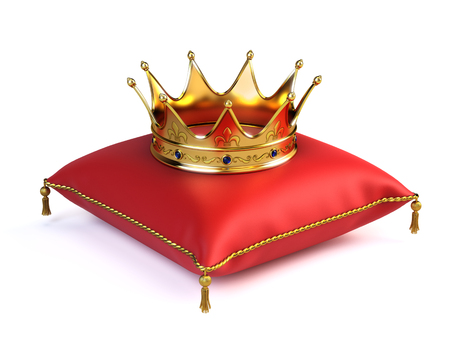 Gold crown on red pillow Фото со стока