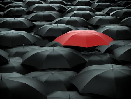 Red umbrella over many black umbrellas