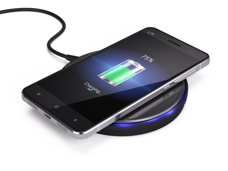 Wireless charging of smartphone isolated on white background