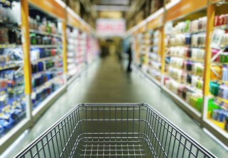 Empty shopping cart in supermarket store interior - retail and shopping concept