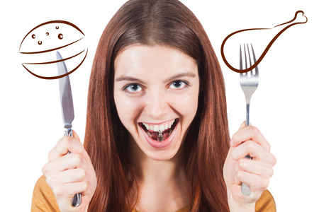 surfeit: Girl with knife and fork preparing for fast food and weight in mouth as a sign of calories