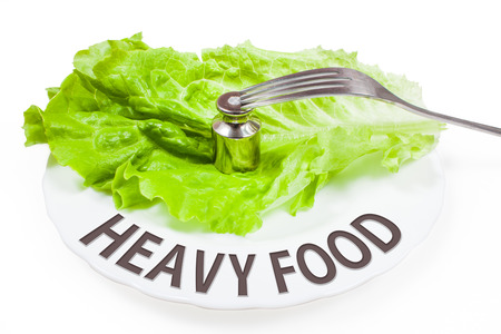 surfeit: Plate with fork and weight. Concept of heavy food. White background