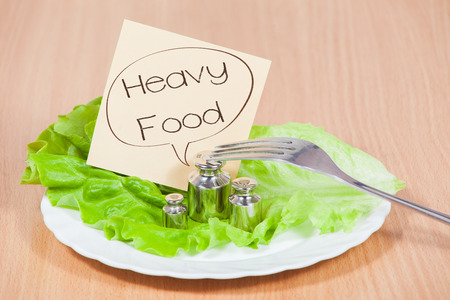 surfeit: Plate with fork and weight on the table. Concept of heavy food. Stock Photo