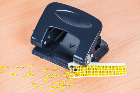 hole punch: Hole punch and extruded paper smiles Stock Photo