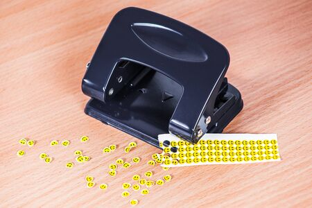 paper punch: Hole punch and extruded paper smiles Stock Photo