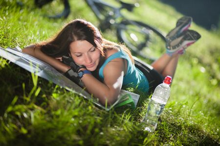 beautifu: Beautifu sport girl lay on a grass with a map near the bicycle Stock Photo