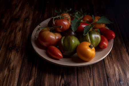 Fresh tomatoes in a wooden plate on a dark wooden background. Harvesting tomatoes. low key Archivio Fotografico