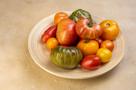 Fresh tomatoes in a wooden plate on a dark wooden background. Harvesting tomatoes Archivio Fotografico